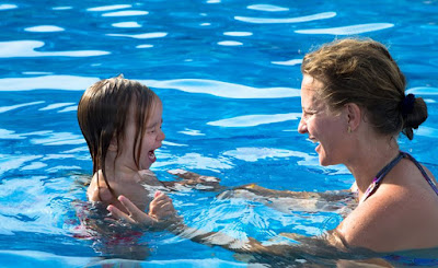 Image of a child and adults in the water facing each other. The child is crying. Behaviour management strategies in dealing with bad behaviour in swimming lessons.