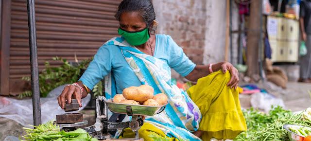 Esta vendedora callejera de verduras en la India porta una mascarilla para protegerse del COVID-19.© UNICEF/Vinay Panjwani