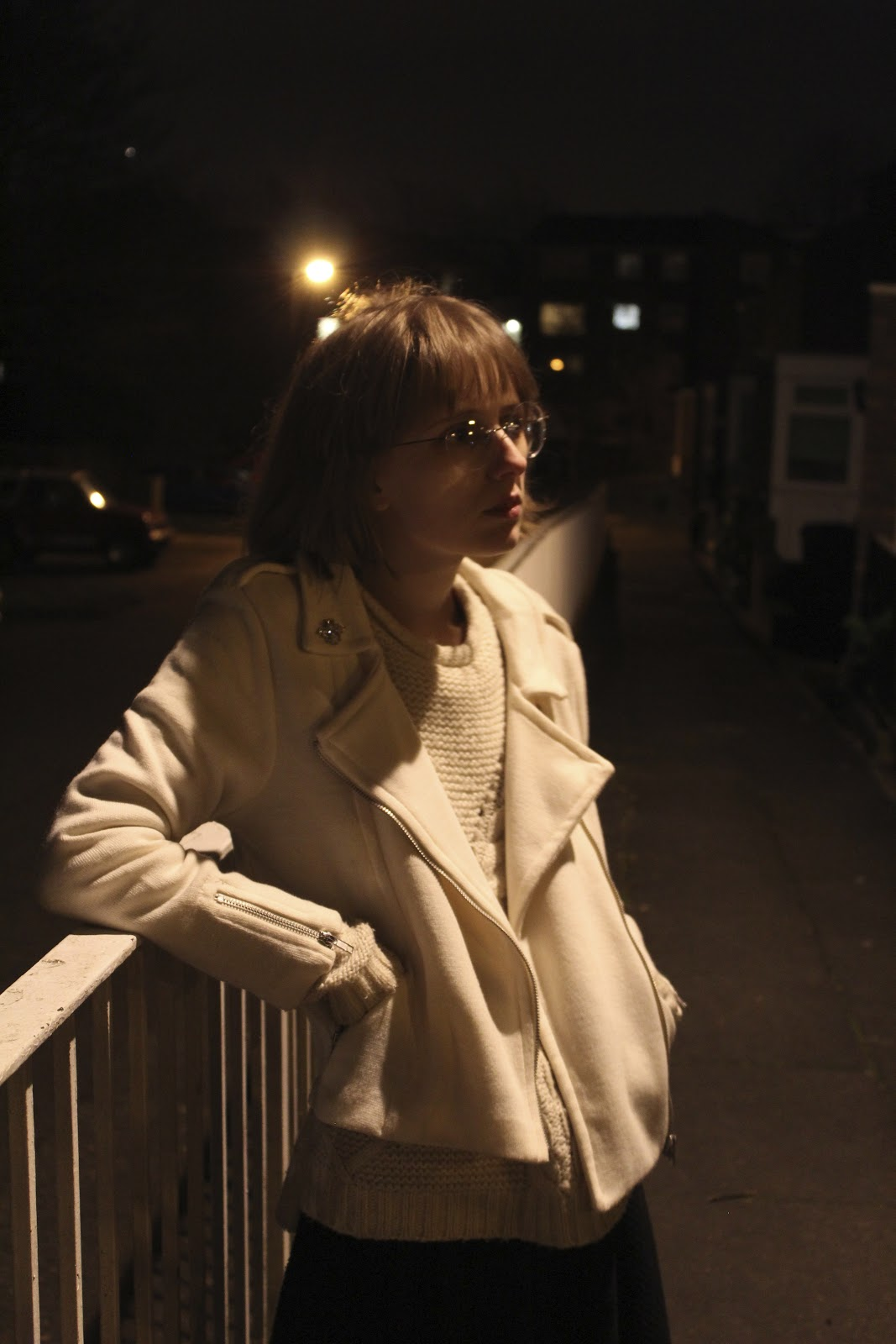 A woman leans against a fence, lit by streetlights overhead.