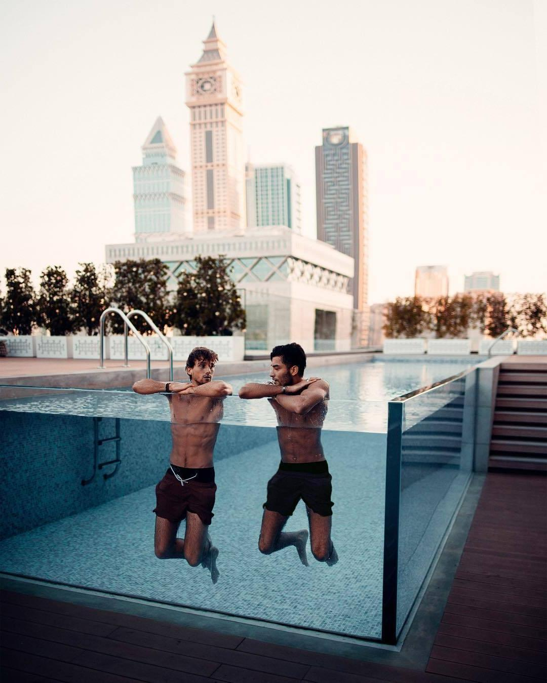 two-buddies-abs-fit-shirtless-dudes-luxurious-pool-impressive-city-view