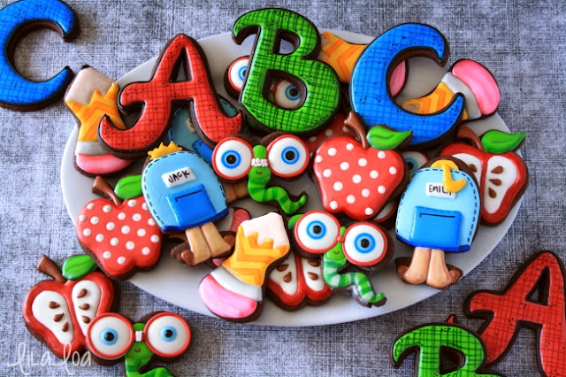 A plate of brightly decorated school sugar cookies -- apples, bookworms, pencils, letters, and backpacks