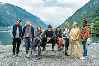 Cast of Ragnarok sitting on a bench beside a lake, mountains in background