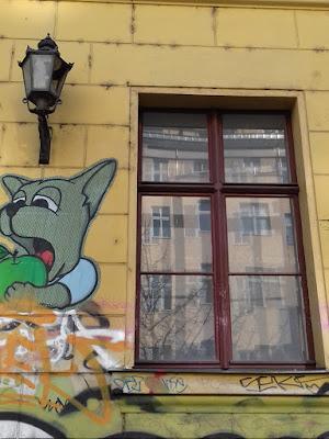 Gelbe Fassade, grüner Apfel, in den jemand reinbeißt