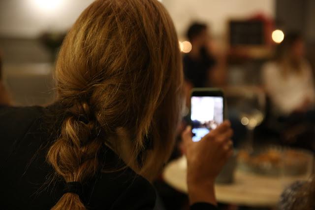 Mujer con trenza vista de espaldas que sujeta un móvil mientras graba.