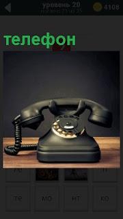 На полке стоит старинный аппарат телефона с диском, по которому раньше звонили