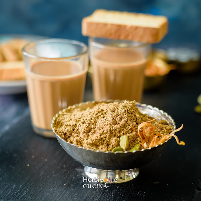 Chai Masala in a bowl with masala chai in the background