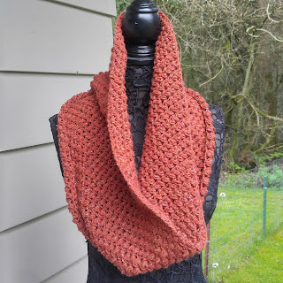 Orange Spring Bean Cowl. This one is slightly larger and the photo is taken outside on a black lace mannequin,