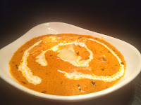 Garnished paneer butter masala in a bowl with cream and butter