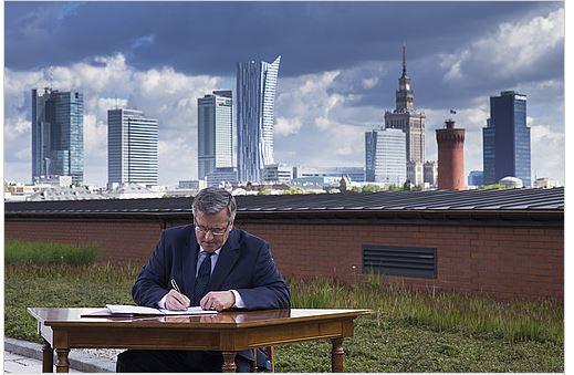 Prezydent Bronisław Komorowski podpisuje ustawę na tle panoramy Warszawy