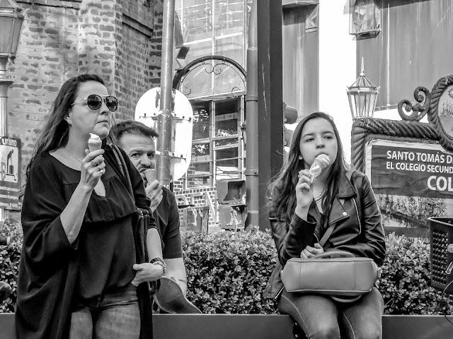 Gente tomado helados en la calle.
