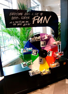 A black circular wheel with small mini black shelve=s filled with cylindrical packets of FUN with a black rectangular sign with FUN in bright white font on a bright background