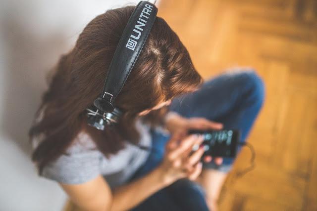 Garota com fones de ouvido ouvindo música