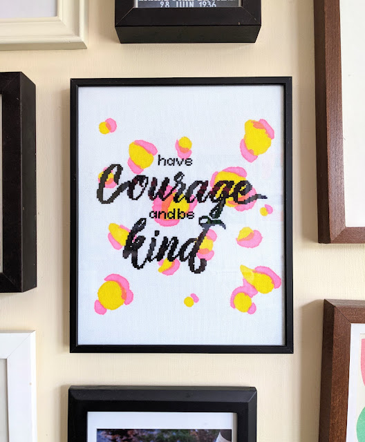 modern framed cross stitch with 'have courage and be kind' cross stiched in black on fabric with hand printed pink and yellow leopard print design in black frame