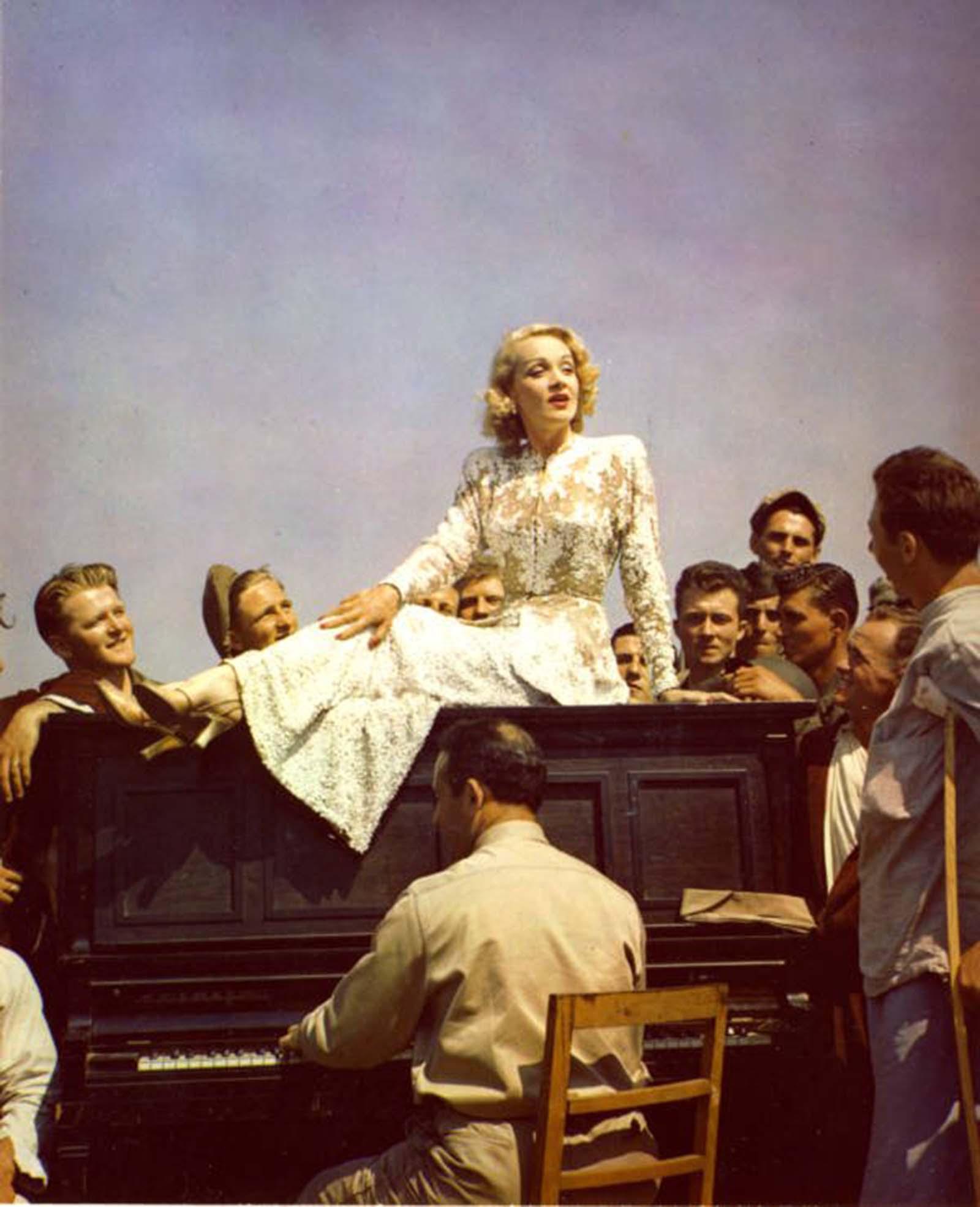 Marlene Dietrich színésznő zongorán ül, miközben a csapatok köré gyűlnek.  Olaszország.  1945.