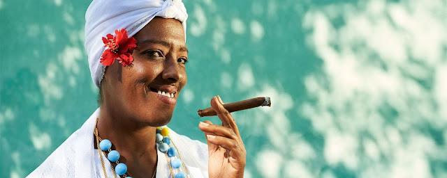 Femme cubaine en tenue traditionnelle qui fume un cigare