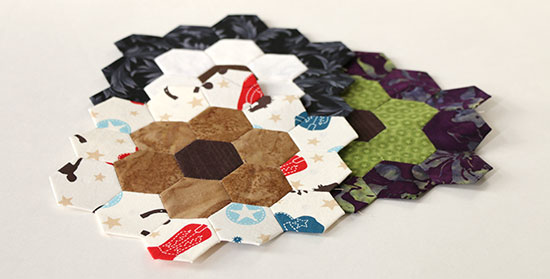 EPP hexies in multiple colors overlapping on a white background.
