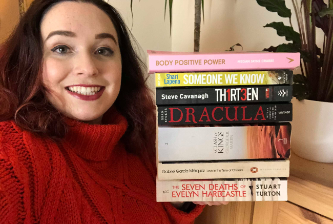 Steph wearing an orange jumper holding a book stack on top of her palm