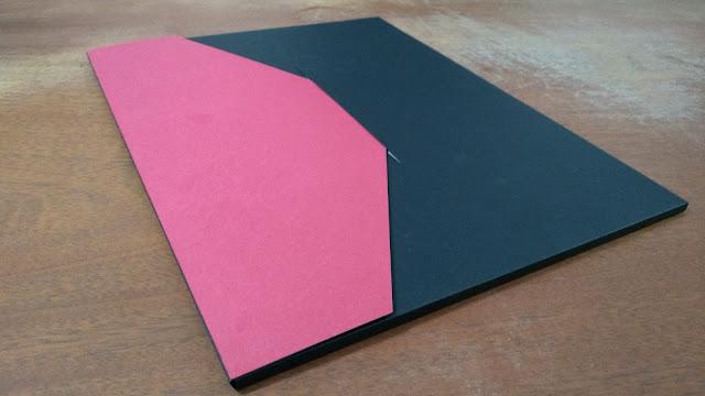 Envelope preto com aba vermelha fechado.