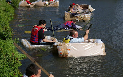 a stag do in boats made of Cardboard racing across a lake in Reading