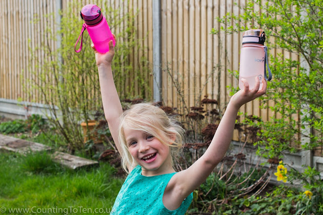 A young girl holding a water bottle in each hand up in the air