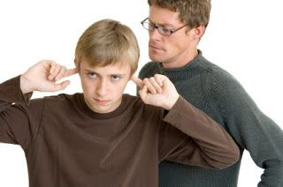 Padre hablando, hijo adolescente tapándose los oídos