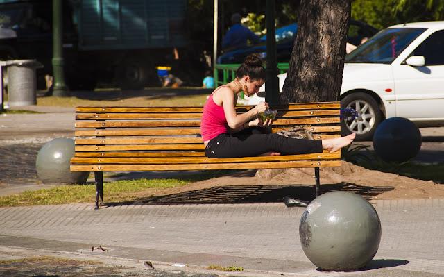 Foto de mujer joven almorzando al sol en un banco de plaza