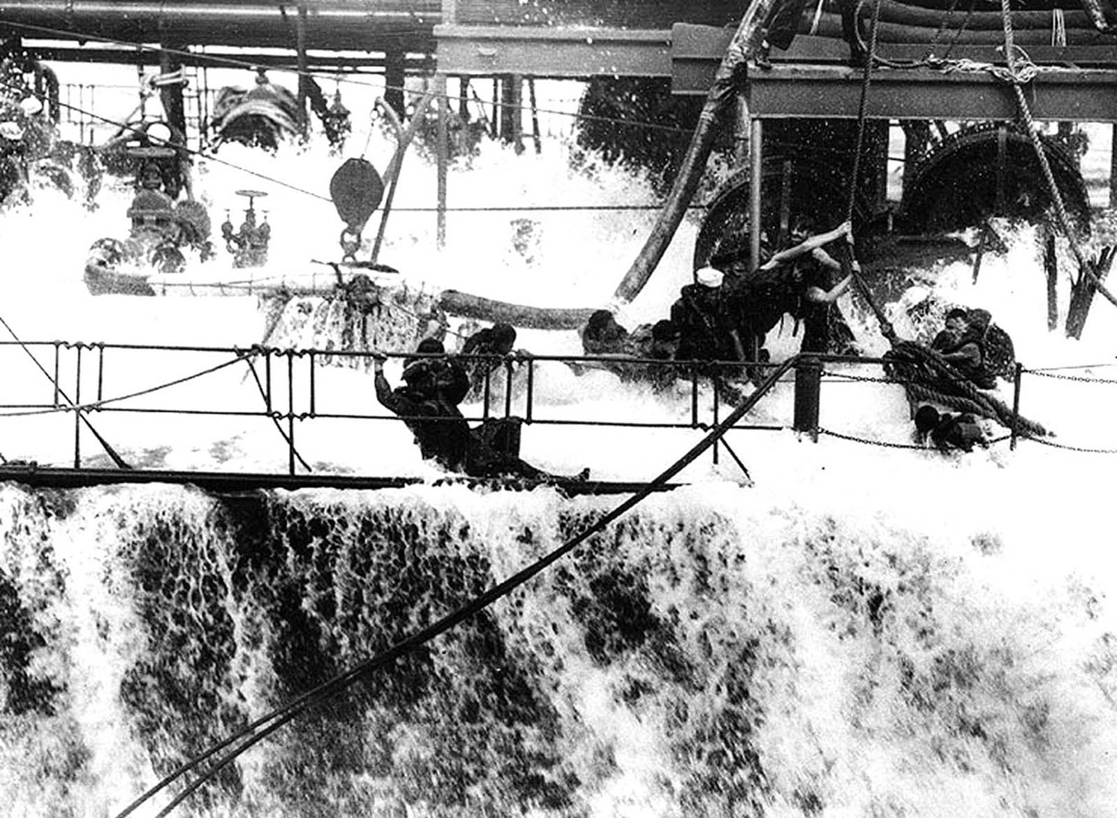 A wave breaks over the main deck of the fleet oiler USS Neosho, engulfing the hose crew, as she refuels USS Yorktown in early May 1942, shortly before the Battle of Coral Sea in the South Pacific. The Neosho was lost in that battle.
