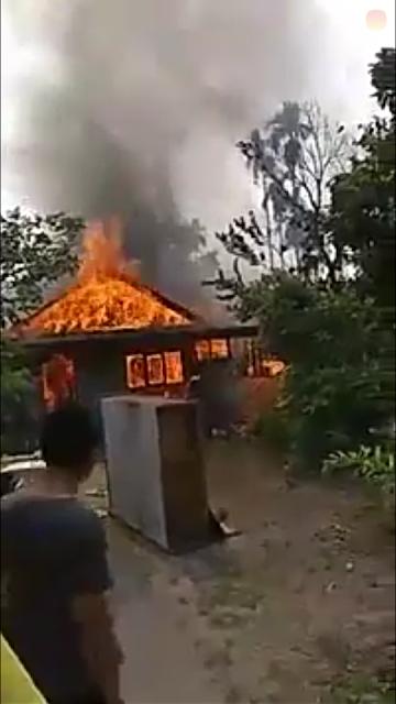 Warga menyaksikan rumah yang terbakar di Langkat