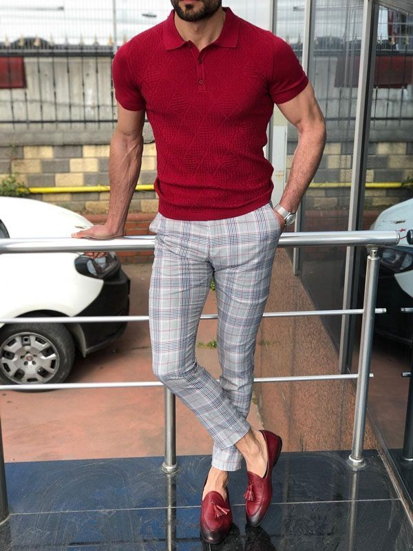 A man wearing maroon color polo shirt and grey chinos.