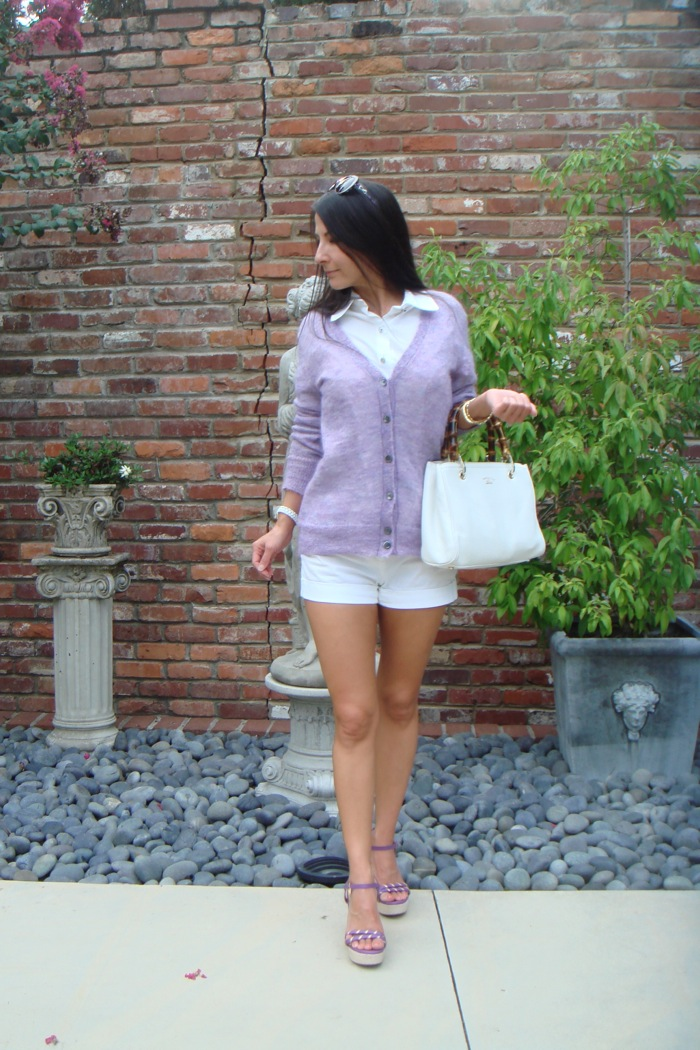 Wearing lavender mohair cardigan over white button down with white shorts. Holding white purse and wearing purple sandals.