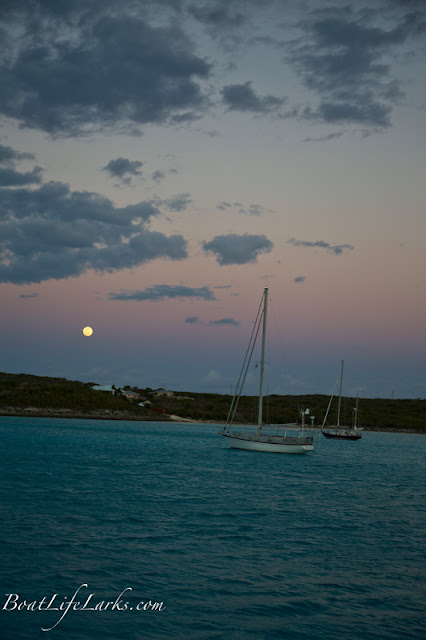 Sailboats anchored in front of full moon, Thompson Bay, Long Island