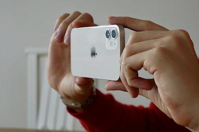 يد تحمل هاتف وتلتقط صور فيديو بهاتف أيفون