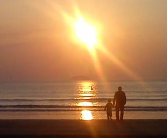 Man and Boy Sillhouetted Against Sunset