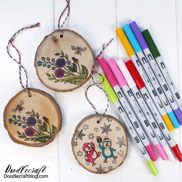 Make darling wood slice ornaments with stamps from Dare 2B Artzy and Tombow ABT PRO Alcohol-Based Markers. They make great ornaments, gift tags and handmade gifts.  Did you know you can use ABT PRO Markers on surfaces other than paper? It's true! They are alcohol-based and work great on fabric, like these face masks. They also work great on wood. Wood slices make the perfect ornaments. You can cut your own or find them at craft stores or online.