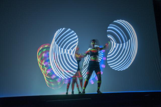 Dançarinas neon performance de abertura de convenção de empresa.