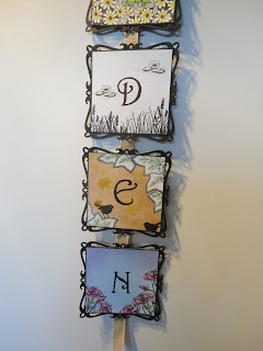 Part of wall hanging, 3 squares with the letters D, E, N, each decorated with a garden theme