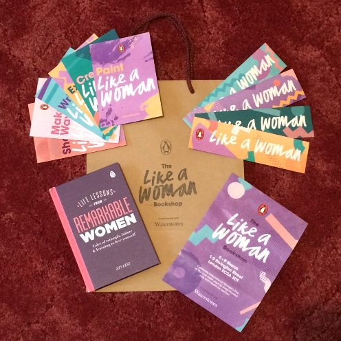 Photo of my purchase, Life Lessons FRom REmarkable Women, along with the Like A Woman paper bag, a Like A Woman leaflet, plus four Like a Woman bookmarks, and six Like A Woman postcards