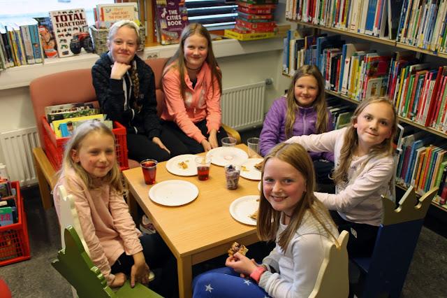 Lina Byre og Hannah Johansen kosar seg i sofaen. Rundt bordet sit Gea Auroa Øiberg, Karina Lyngved, Rubi Marie Øiberg og Sara H. Bosmen