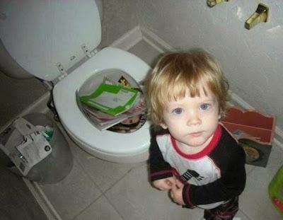 Niño metiendo revistas en la taza de baño o retrete