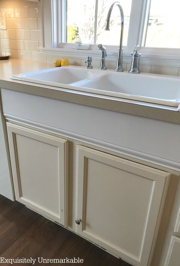 Bisque colored sink base cabinets under a white double sink