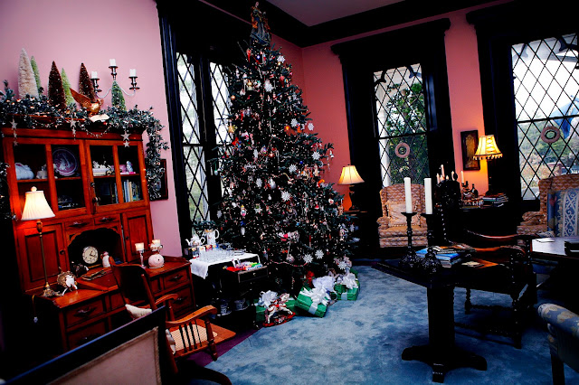 chirstmas trees with many ornaments and lights and desk with garland on top wiht lights and candle stick and large window in the backgroung with wreaths in the window and two chairs in front of each window