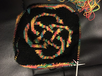 On a circular needle, a black background with a rainbow coloured Celtic knot motif. There are sections of rainbow colours just visible on two sides of the center square