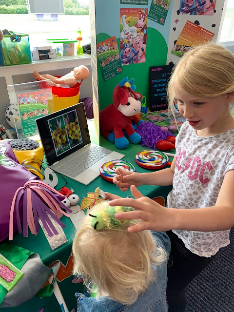 Two children Playing with puppets at the Moo Music Stall