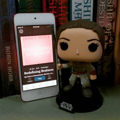A Funko bobblehead of Rey from Star Wars stands next to a white iPod with Redefining Realness's pink cover on its screen. the iPod leans up against a shelf full of Robin Hobb novels.