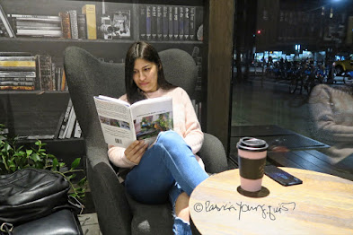 "This ;picture features a young woman with straight black hair. She is curled up in an upholstered  chair and reading ""Words In Our Beak Volume Two.""  There is a bookshelf behind her and in front of her to the right is a paper container for a hot beverage. It has a black lid. The woman seems engrossed in the book. Information re this book as well as info re volumes one and three is on my blog @ https://www.thelastleafgardener.com/2018/10/one-sheet-book-series-info.html"