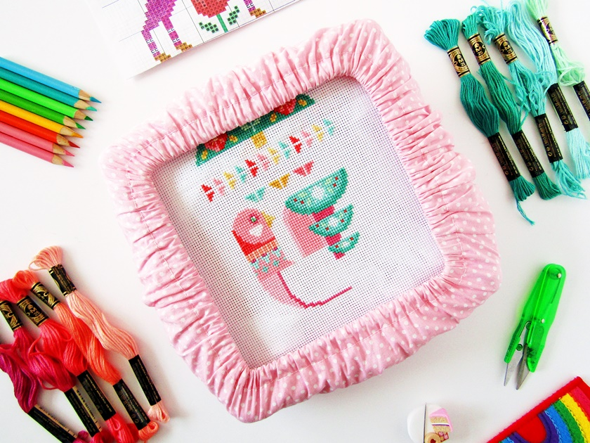 An in-progress photo of a Satsuma Street Deck the Halls Wall Hanging cross stitch, showing a partially completed pink Scandinavian-style bird cross stitch on white aida in a pink polka dot embroidery frame in the centre of the photo, surrounded by a range of pink and teal threads, fluorescent green embroidery scissors, a cake needle minder and needle, coloured pencils, and a cross stitch pattern.