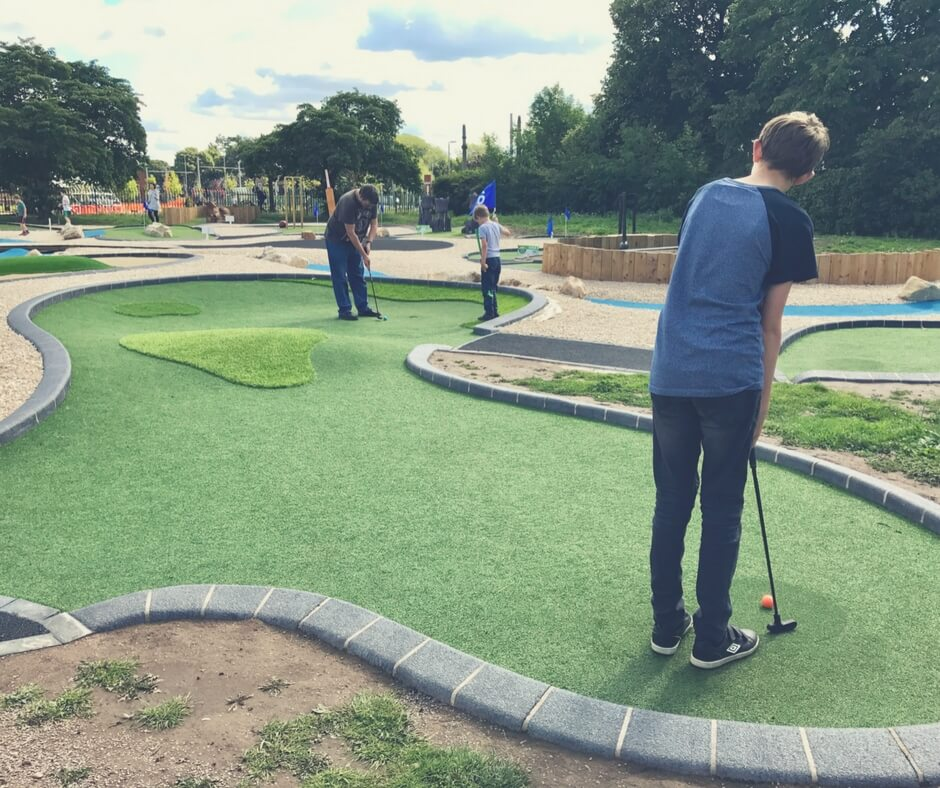 2 boys and their father play mini golf in Highfields Park in Nottingham. The father is taking his shot close to the hole as the youngest boy watches.