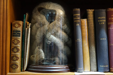 Part of a shelf filled with old books with legal titles and a glass dome with a barrister's wig inside.