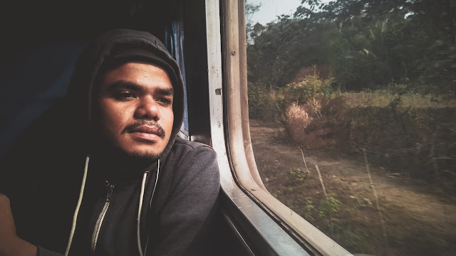 teman traveling saya, Yoman sedang berpose di kaca jendela kereta api lokal menuju merak