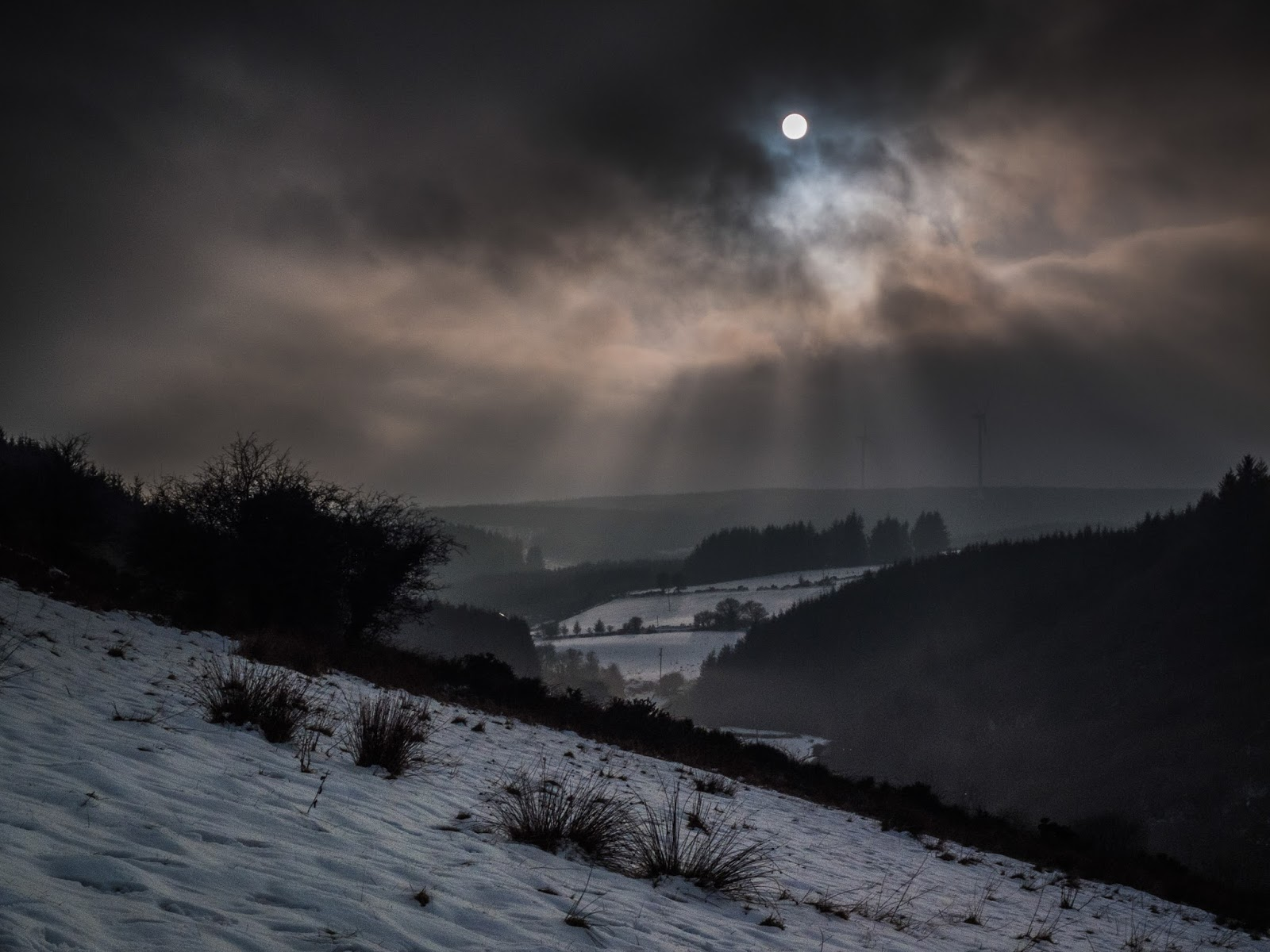 Irish mountain landscape in the snow with dramatic skies and crepuscular sun rays.